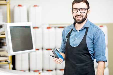 Portrait of a male worker standing near the operating desk of the printing manufacturing