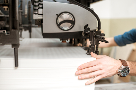 Feeling paper sheets into the printing machine at the manufacturing