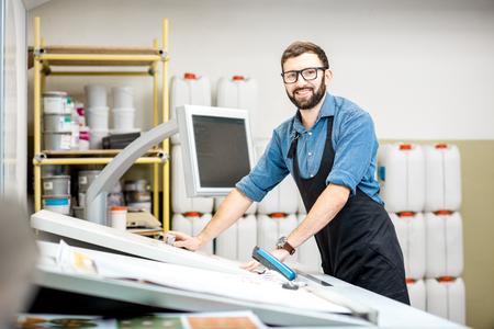 Retrato de un trabajador masculino de pie cerca de la mesa de operaciones de la fabricación de impresión