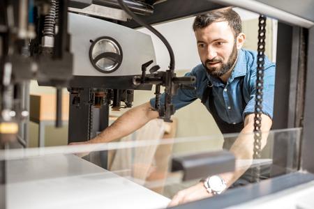 Mężczyzna pracujący z arkuszami papieru wczuwającymi się w maszynę drukarską w produkcji