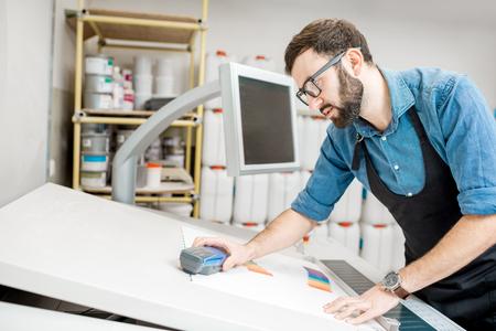 Lavoratore dell'uomo che misura colore di stampa con lo spettrometro sulla scrivania dell'impianto di stampa