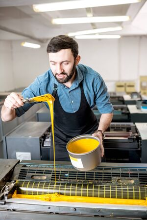 Typographer filling yellow paint into the offset machine at the printing manufacturing