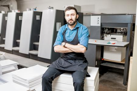Ritratto di un tipografo bello in piedi presso la produzione di stampa con macchina offset sul backgorund