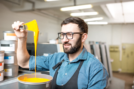 Typographer stiring yellow paint for offset machine standing at the printing manufacturing Stock Photo
