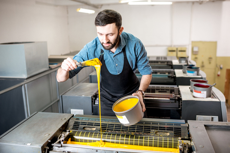 Typographer filling yellow paint into the offset machine at the printing manufacturing Reklamní fotografie - 95997062