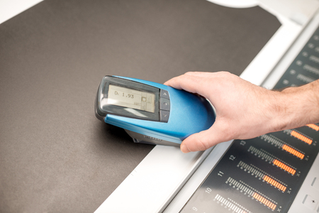 Measuring depth of the black color with spectrometer tool at the operating desk of the printing plant Stock Photo