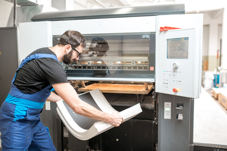Worker in unifrom getting printed sheets from the offset machine at the printing manufacturing Stok Fotoğraf