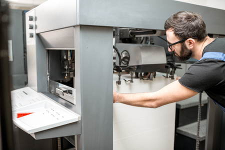 Worker filling up the paper sheets for printing into the offset printing machine at the manufacturing