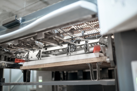 Fragment of the offset printing machine during the printing at the manufacturing Imagens