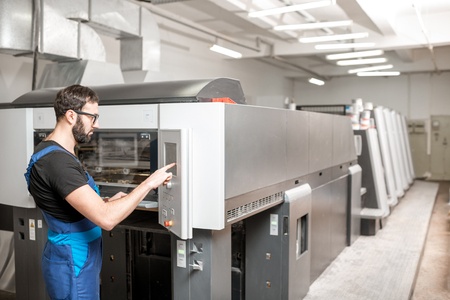 Printing operator working with offset machine at the printing manufacturing