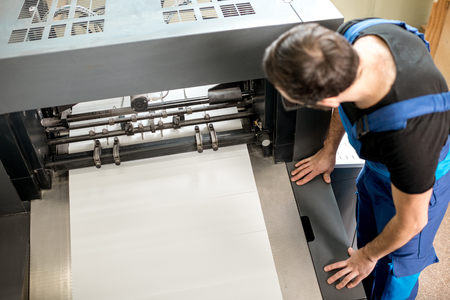 Worker following a printing process on the offset machine at the manufacturing Stok Fotoğraf