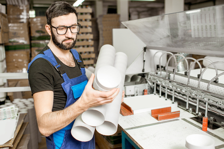 Portrait of a handsome worker in unifrom standing with paper tubes at the old printing manufacturing Stock Photo