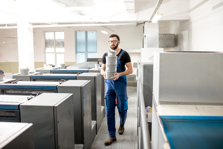 Typographer carrying paint buckets walking on the offset machine at the printing manufacturing Stock Photo