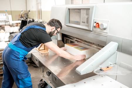 製造時に切断機に紙を積み重ねて均一な労働者