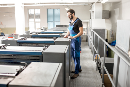 Worker in uniform supervising offset printing machine at the manufacturing