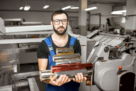 Handsome worker holding foil rolls for stamping standing at the vintage printing manufacturing