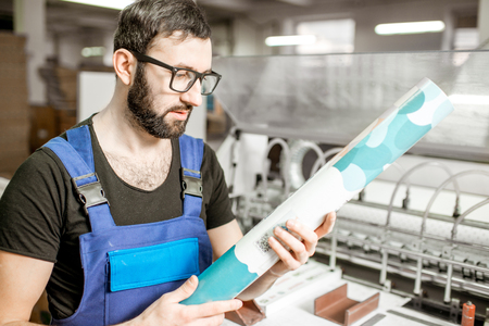 Man checking the quality of the paper tube at the printing manufacturing Reklamní fotografie