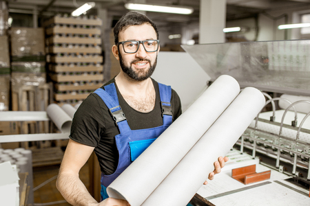 Portrait of a handsome worker in unifrom standing with paper tubes at the old printing manufacturing Banco de Imagens