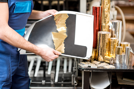 Worker checking the quality of the foil stamping at the manufacturing