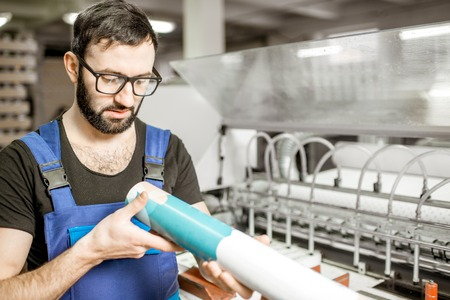 Man checking the quality of the paper tube at the printing manufacturing Banco de Imagens