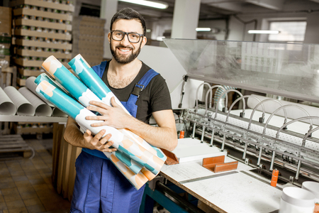 Portrait of a handsome worker in unifrom standing with paper tubes at the old printing manufacturing Reklamní fotografie