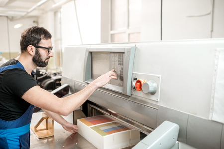 Worker in uniform operating with touch screen professional cutting machine at the manufacturing
