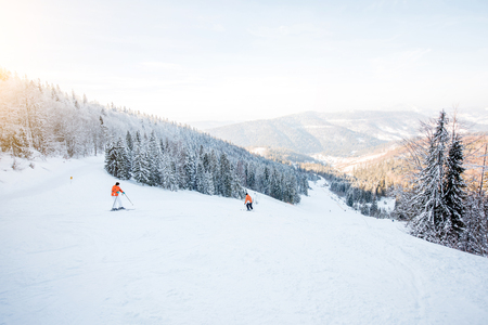 Landscape view on the beautiful Carpathian mountains with ski slope and skiers during the sunny weather