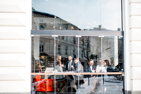 Business people during the coffee break sitting with laptops near the window. General view through the window with city reflection and copy space