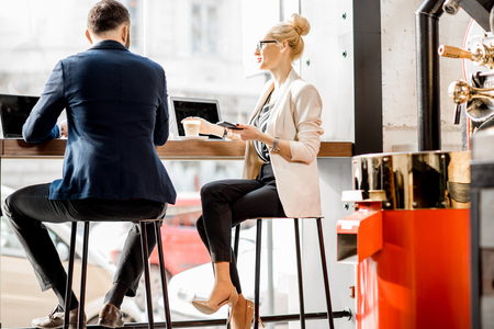 Business couple talking during the coffee break sitting near the window in the cafe Stock Photo