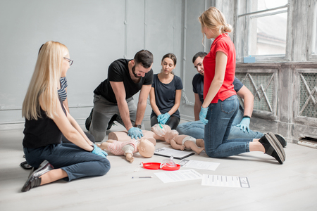 Group of people learning how to make first aid heart compressions with dummies during the training indoors Archivio Fotografico - 97240491