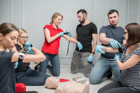 A group of people learning to apply the tourniquet to prevent bleeding during the first aid training indoors