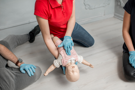 Woman instructor showing how to make chest compressions on a baby dummy during the first aid group training indoors