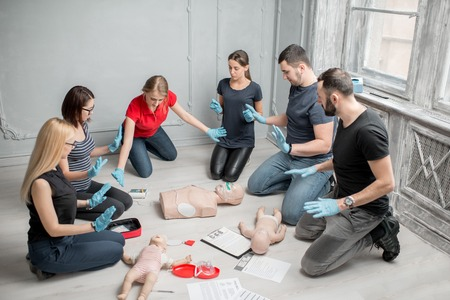 Stay away moment during the defibrillation process on a first aid group training indoors Archivio Fotografico - 97864286