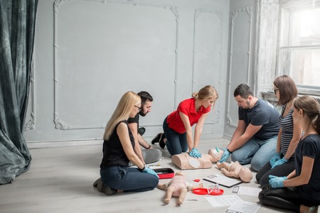 Group of people learning how to make first aid heart compressions with dummies during the training indoors Archivio Fotografico - 97864395