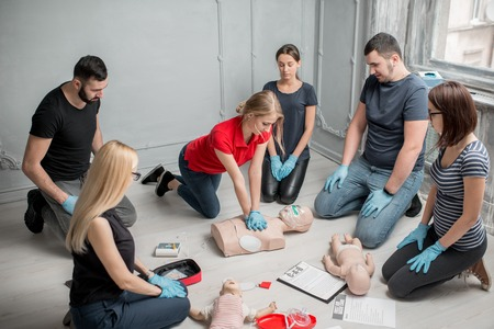 Group of people learning how to make first aid heart compressions with dummies during the training indoors Stock fotó - 97864398