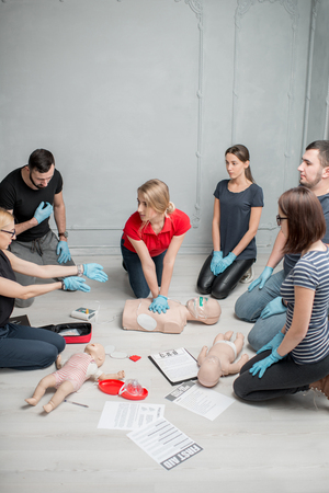 Group of people learning how to make first aid heart compressions with dummies during the training indoors Archivio Fotografico - 97864869