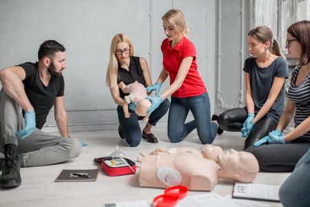 Personas que aprenden cómo salvar una vida cuando el bebé se atraganta sentado junto con el instructor durante el entrenamiento de primeros auxilios en interiores