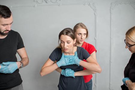 Instructor que muestra cómo salvar una vida cuando el ser humano se ahoga de pie durante el entrenamiento de fisr aid en interiores