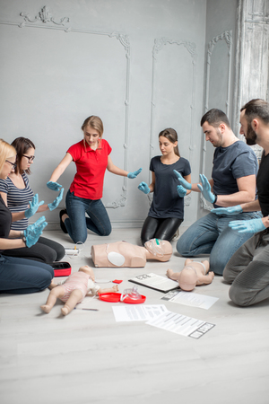 Stay away moment during the defibrillation process on a first aid group training indoors Archivio Fotografico - 97864459