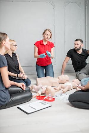 屋内の応急処置グループ訓練中に人工呼吸用バルブを示す若い女性インストラクター 写真素材