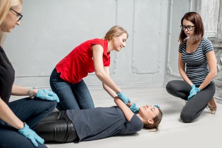 Instructora joven que muestra cómo acostar a una mujer durante el primer entrenamiento de asistencia médica en interiores Foto de archivo