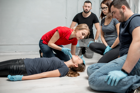 Young woman instructor showing how to lay down a woman during the first medical aid training indoors Stock fotó - 97864847