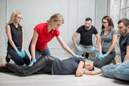 Instructora joven que muestra cómo acostar a una mujer durante el primer entrenamiento de asistencia médica en interiores