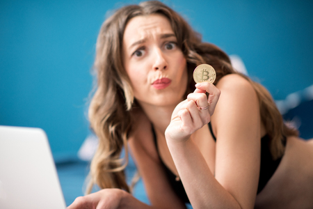 Young woman holding golden crypto coin with frustrated expression of the face, lying with laptop on bed at home Reklamní fotografie