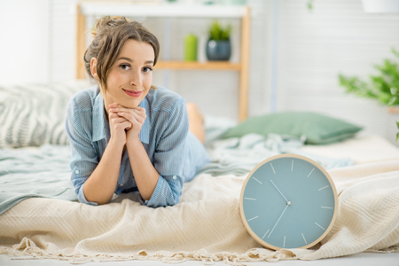 Portrait of a cute woman lying with alarm clock in the cozy and bright bedroom at home Stockfoto