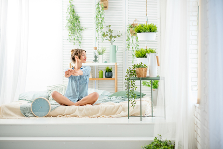 Young woman having a good morning sitting on the bed in the beautiful bright bedroom with green plants and clock Stockfoto - 97459609