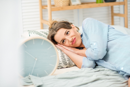 Young and beautiful woman in blue shirt lying and looking with confused emotions on a big alarm clock in the bedroom Stockfoto - 97459296