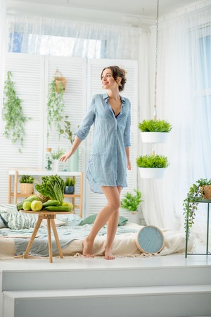 Full length portrait of a woman waking up standing in the white and cozy bedroom with green plants