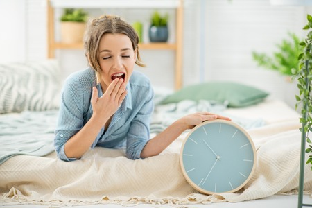Portrait of a beautiful sleepy woman turning off the alarm clock lying in the cozy and bright bedroom at home Stockfoto