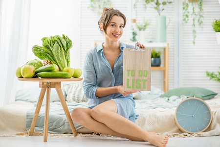 Portrait of a young and beautiful woman sitting with healthy fresh food and list in the bright living room with green plants at home